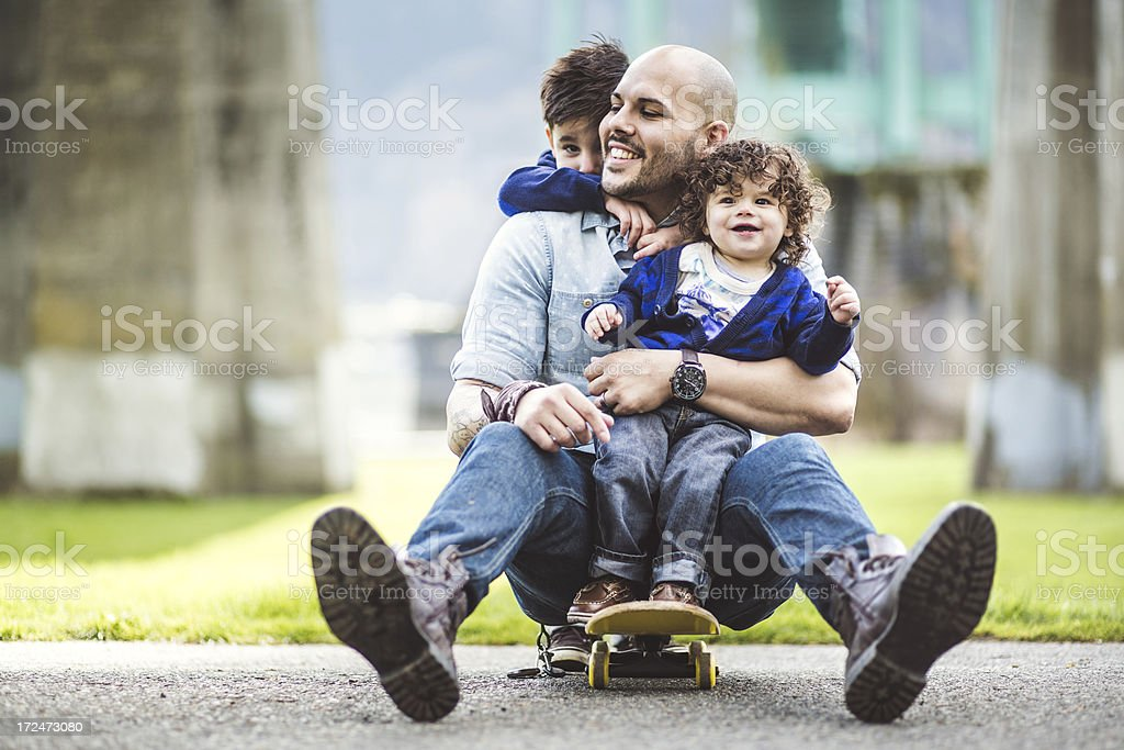 Dad on a skateboard at a park with two sons stock photo