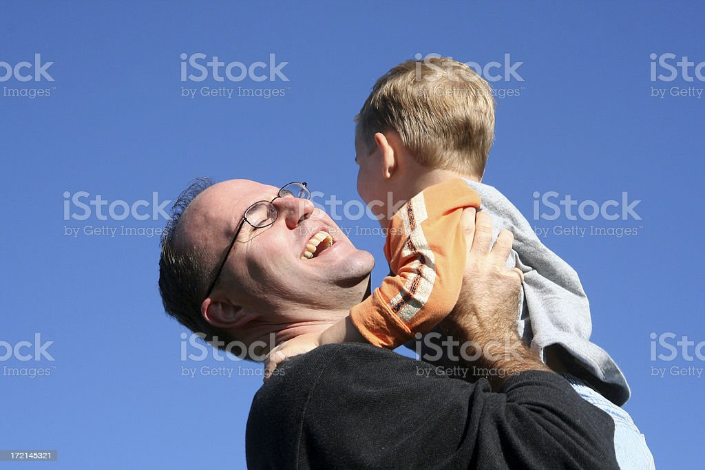 Dad Picking Up His Little Boy Playing Outdoors royalty-free stock photo