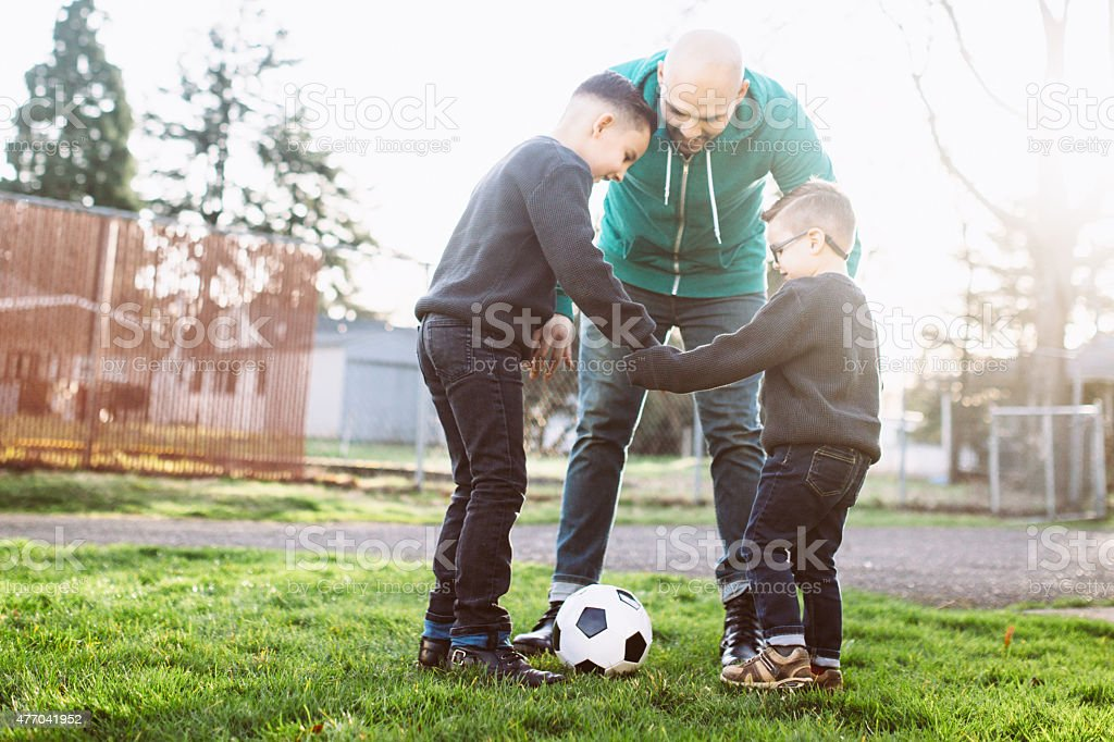 Dad Playing Soccer with His Sons stock photo