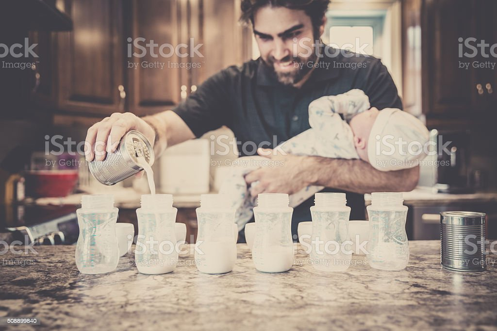Dad Preparing Baby Bottles stock photo