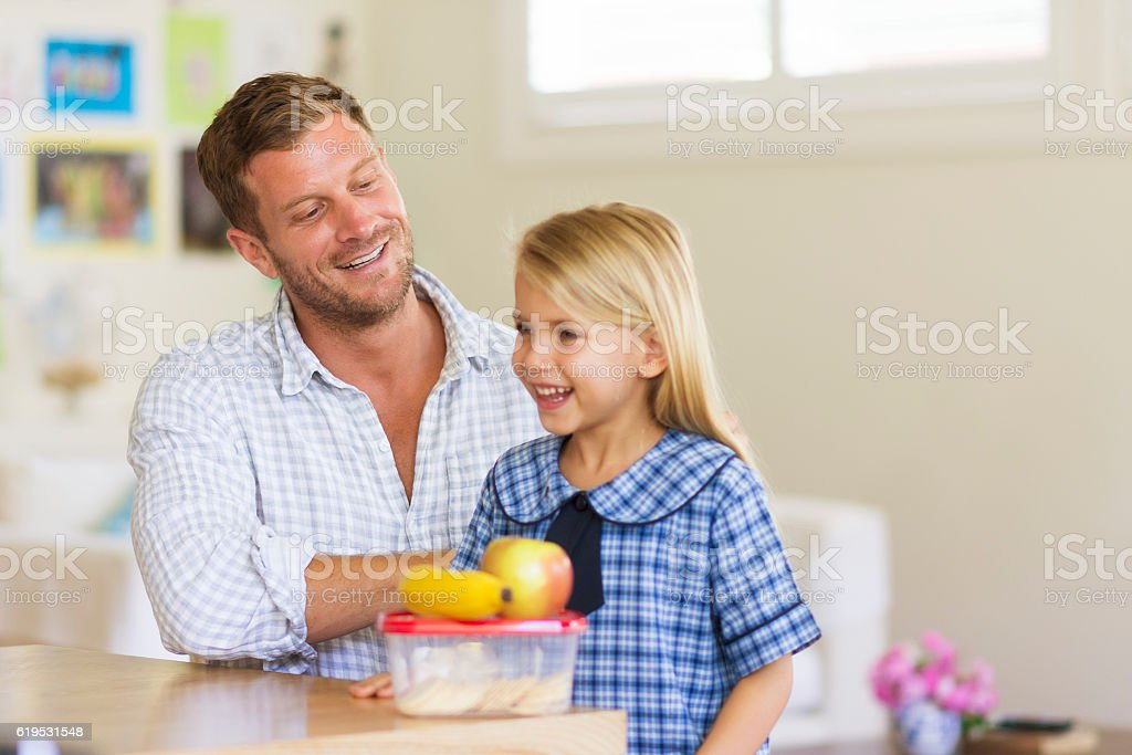 Dad preparing daughter for school stock photo