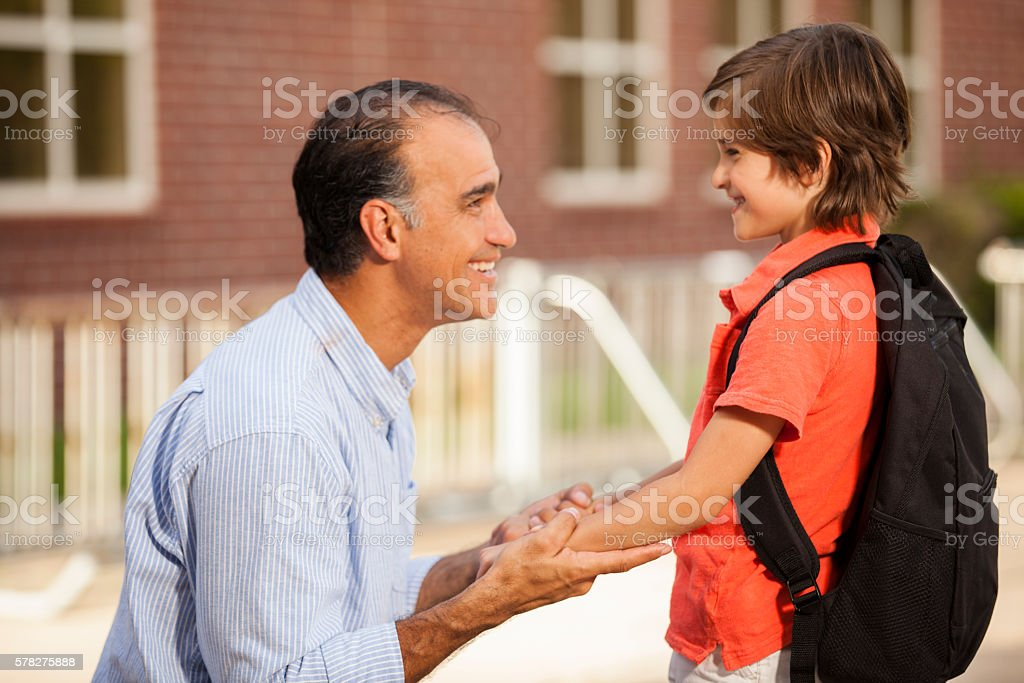 Dad reassures nervous boy on first day of school. stock photo