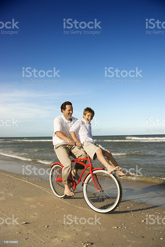 Dad riding red bicycle with son on handlebars. stock photo