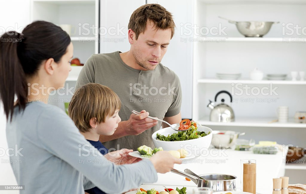 Dad serving salad to his family for lunch stock photo