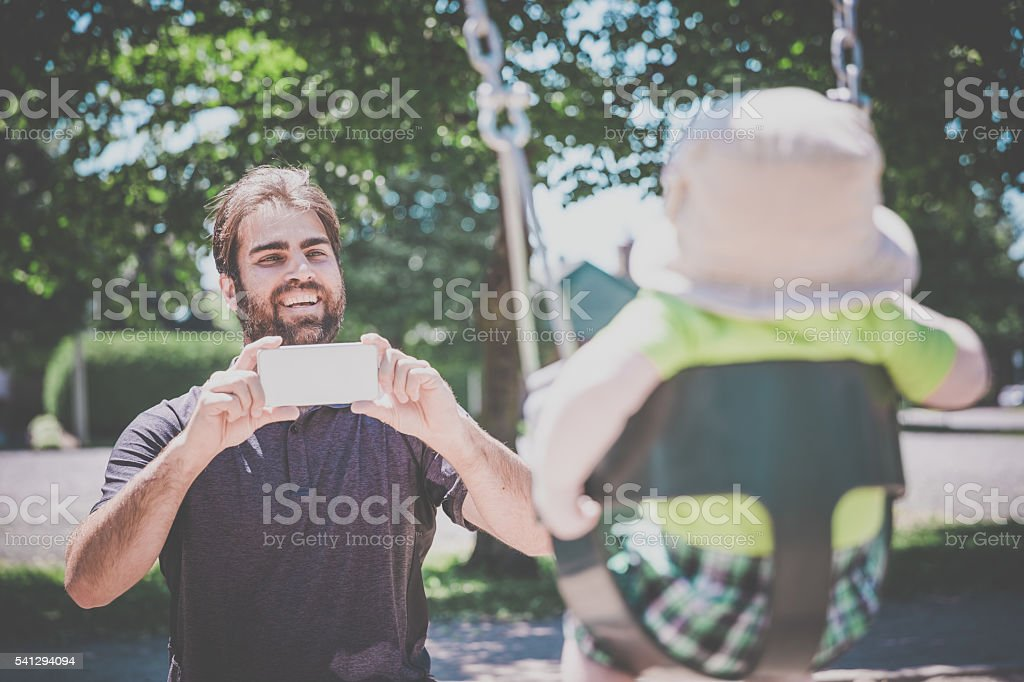 Dad Taking Pictures of Baby in Playground Swing Outdoors stock photo