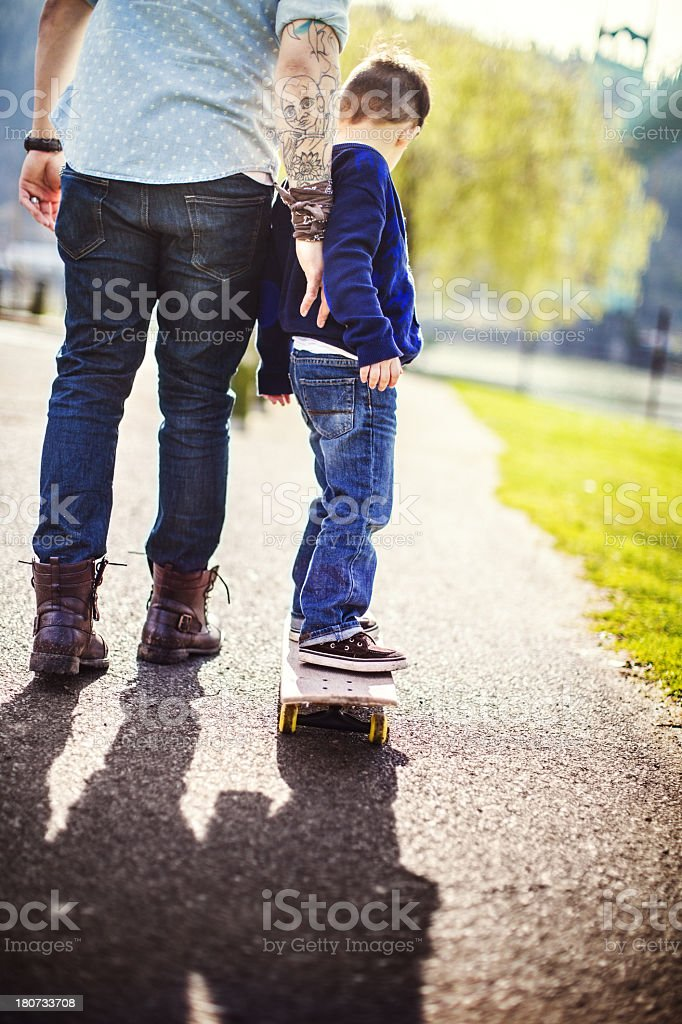 Dad Teaching His Son to Skateboard royalty-free stock photo