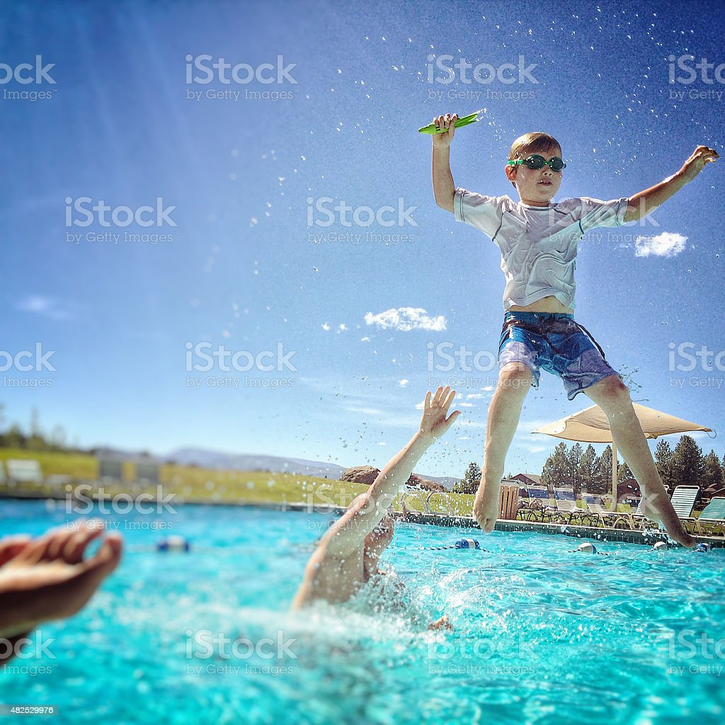 Dad throws son in the air while in pool stock photo
