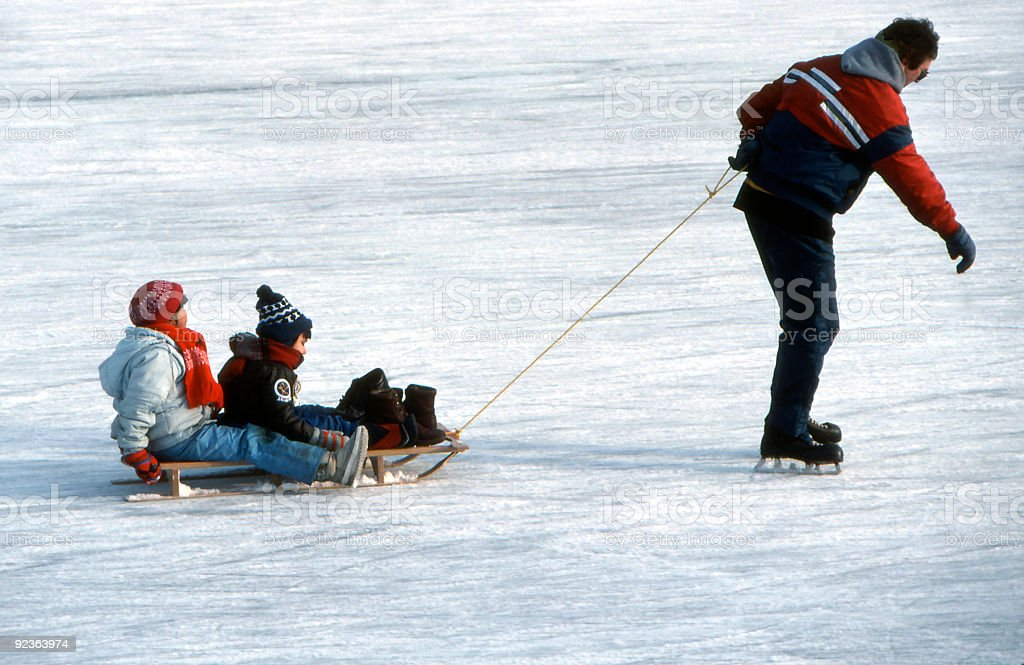 Dad Towing Kids on Ice Rink stock photo