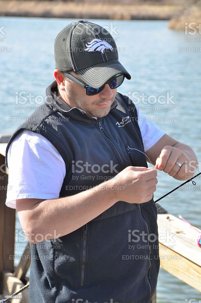 Dad Tying a a hook onto his daughters fishing line. stock photo