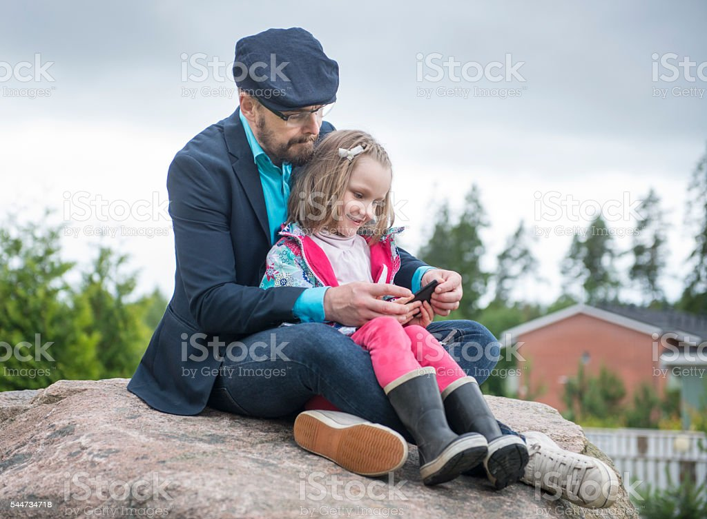 Dad using smartphone with daughter. stock photo