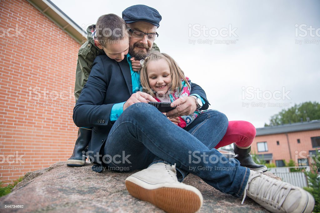 Dad using smartphone with kids. stock photo