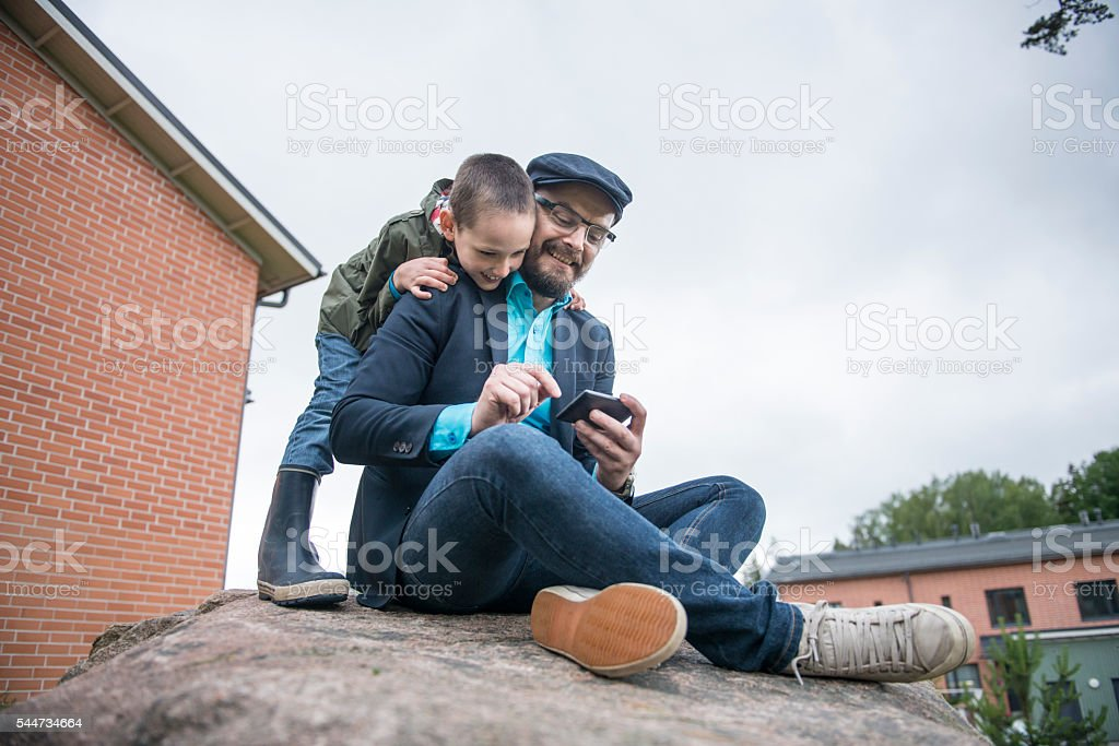 Dad using smartphone with son. stock photo