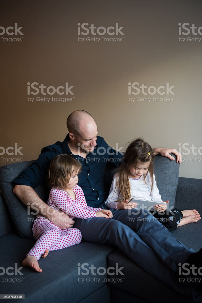 Dad watching movie with daughters stock photo