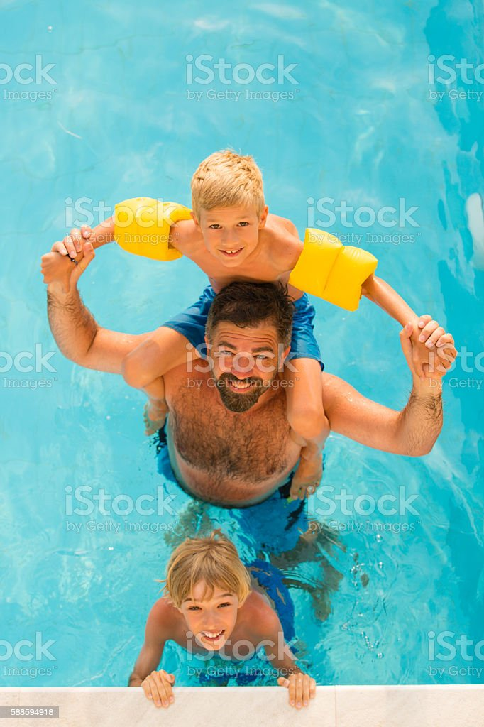 Dad with children in swimming pool stock photo