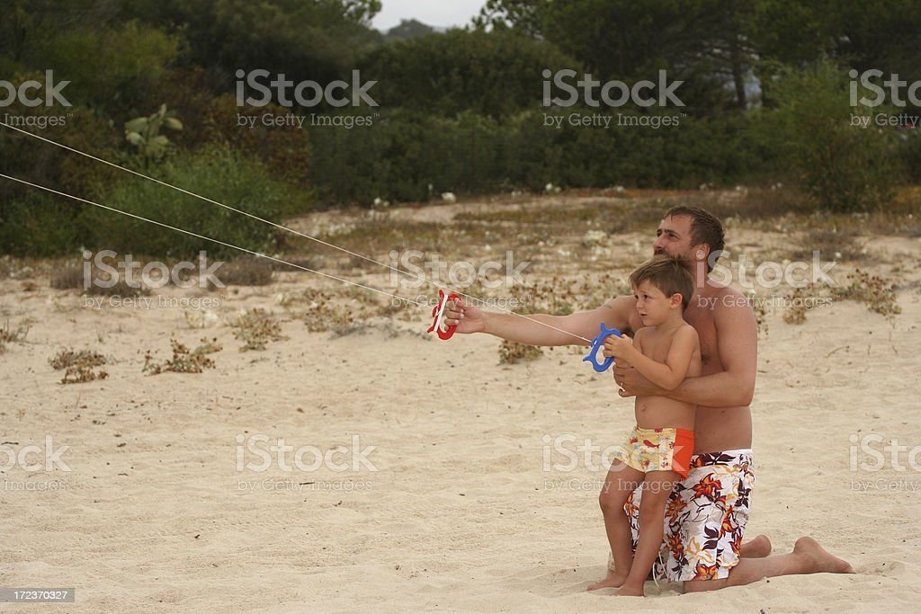 Daddy and son flying an acrobatic kite (two wires) stock photo