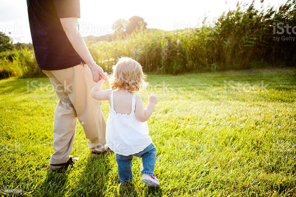 Daddy and Toddler Daughter Walking Outside Holding Hands royalty-free stock photo