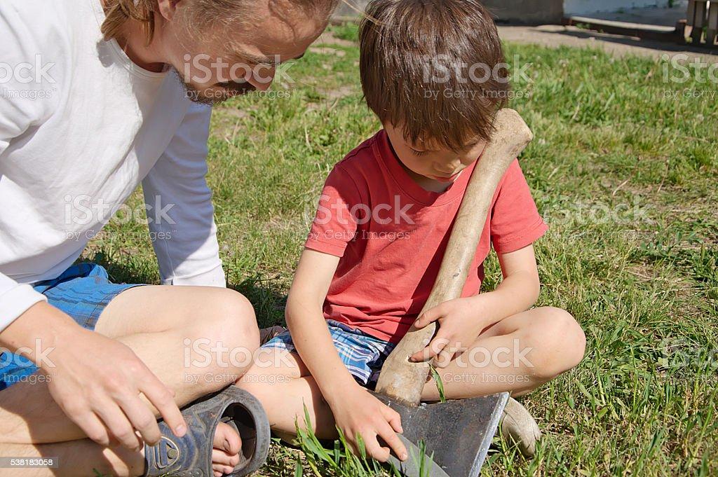 Daddy breeding boy in ax sharpening stock photo