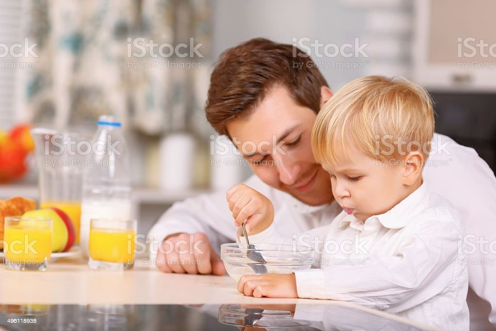 Daddy encourages his son to finish a cereal stock photo