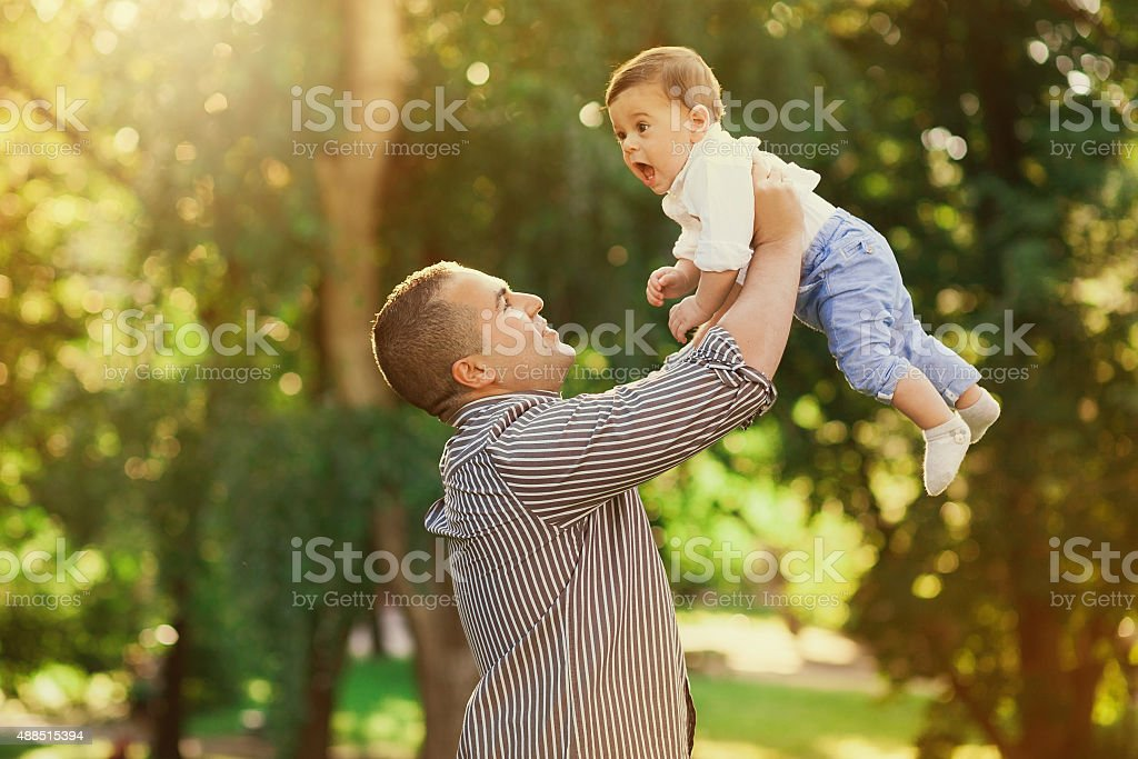 Daddy playing active games with his son outside stock photo