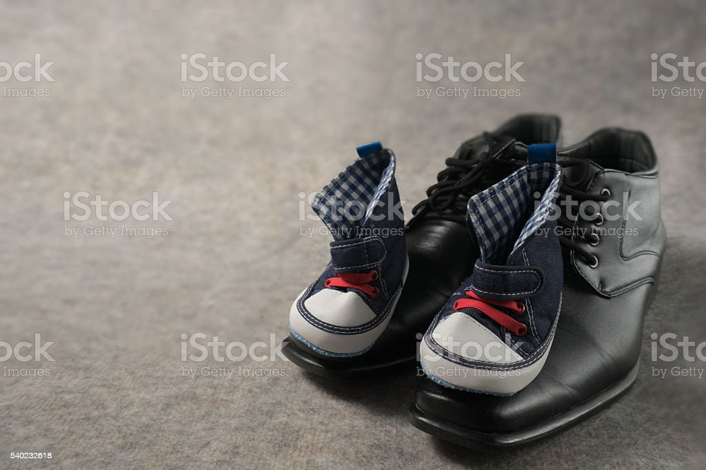 Daddy's boots and baby's sneakers, on wood background, fathers stock photo