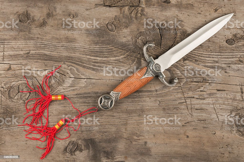 Dagger lying on a wooden surface stock photo