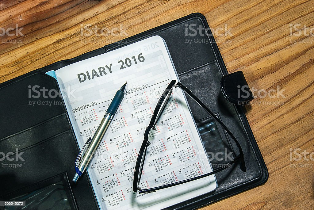 Daily book in black leather case with glasses and pen stock photo