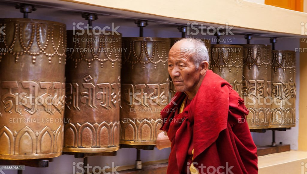 Daily lifestyle of the monks in a Buddhist monastery. A Buddhist monk spins prayer wheels stock photo