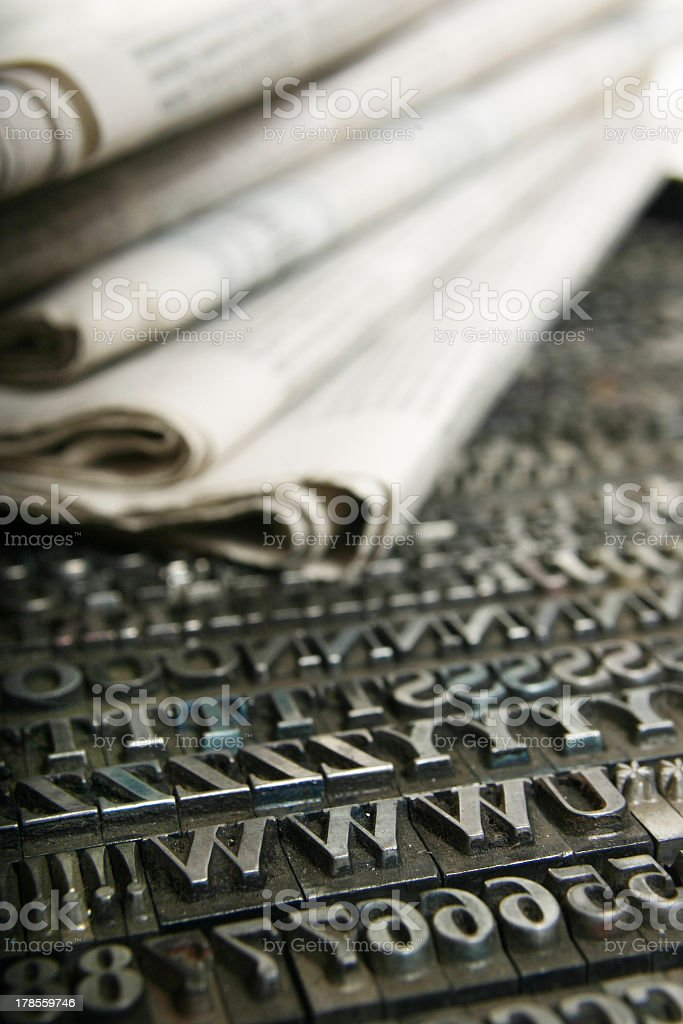 Daily newspapers sitting on top of movable print letters royalty-free stock photo