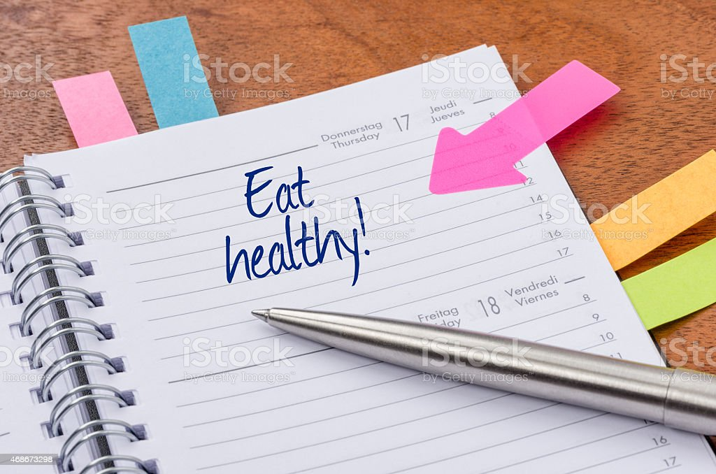 Daily planner with the entry Eat healthy stock photo