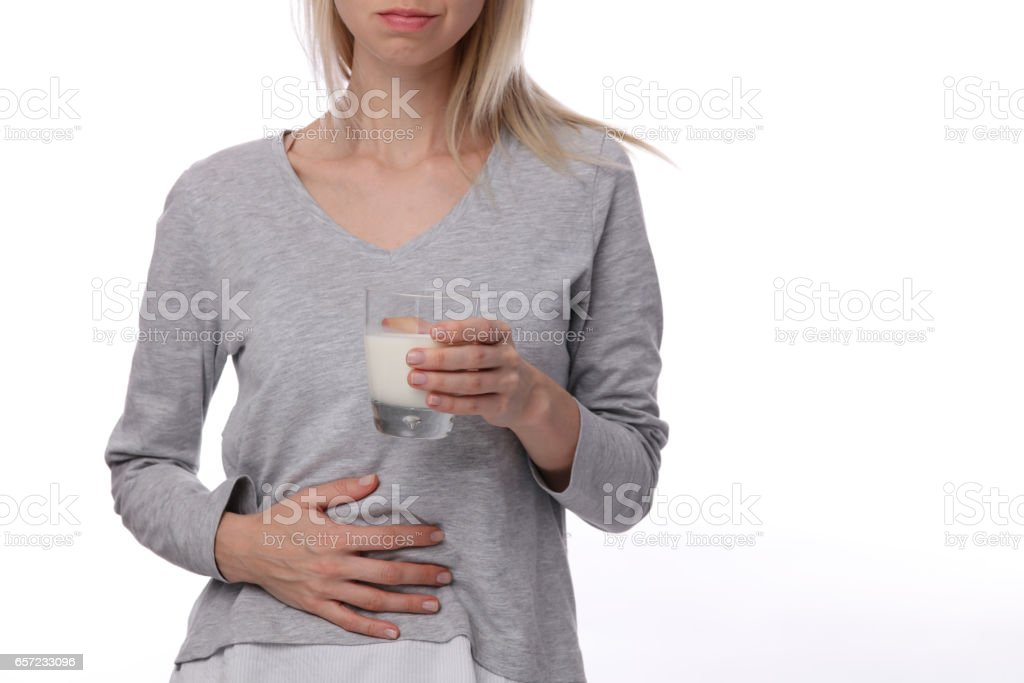 Dairy Intolerant person.Woman with stomach pain holding a glass of milk. Lactose intolerance, health care concept. stock photo