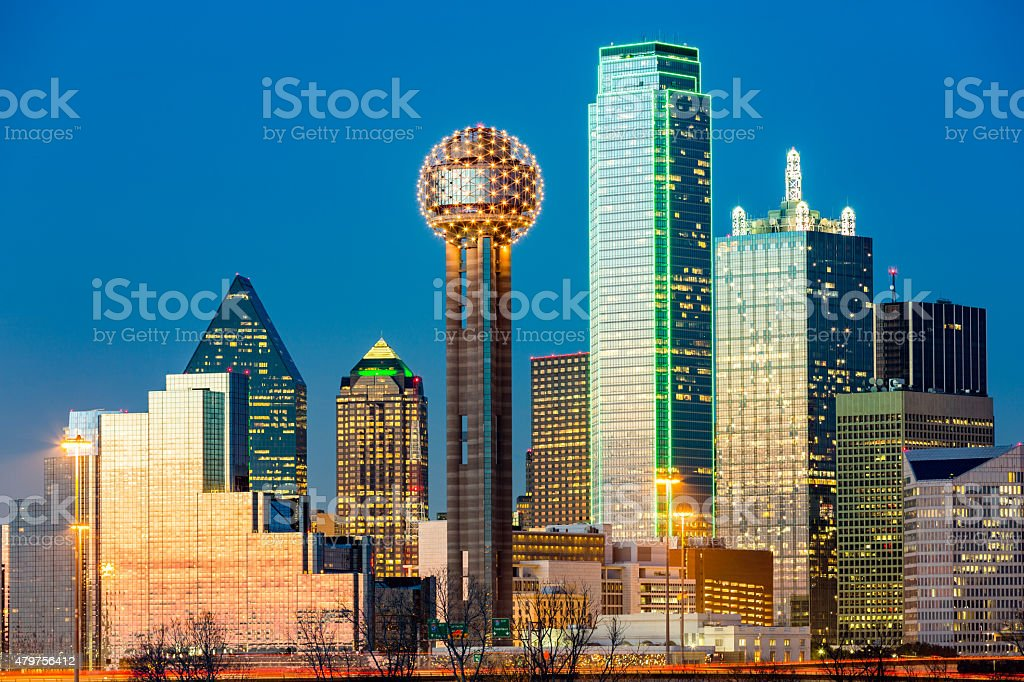 Dallas skyline at sunset under a clear blue sky.