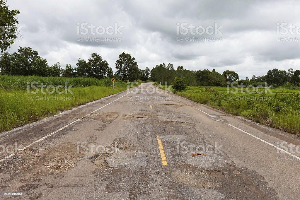 Damaged asphalt pavement road with potholes stock photo