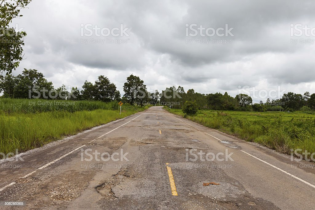 Damaged asphalt pavement road with potholes stock photo