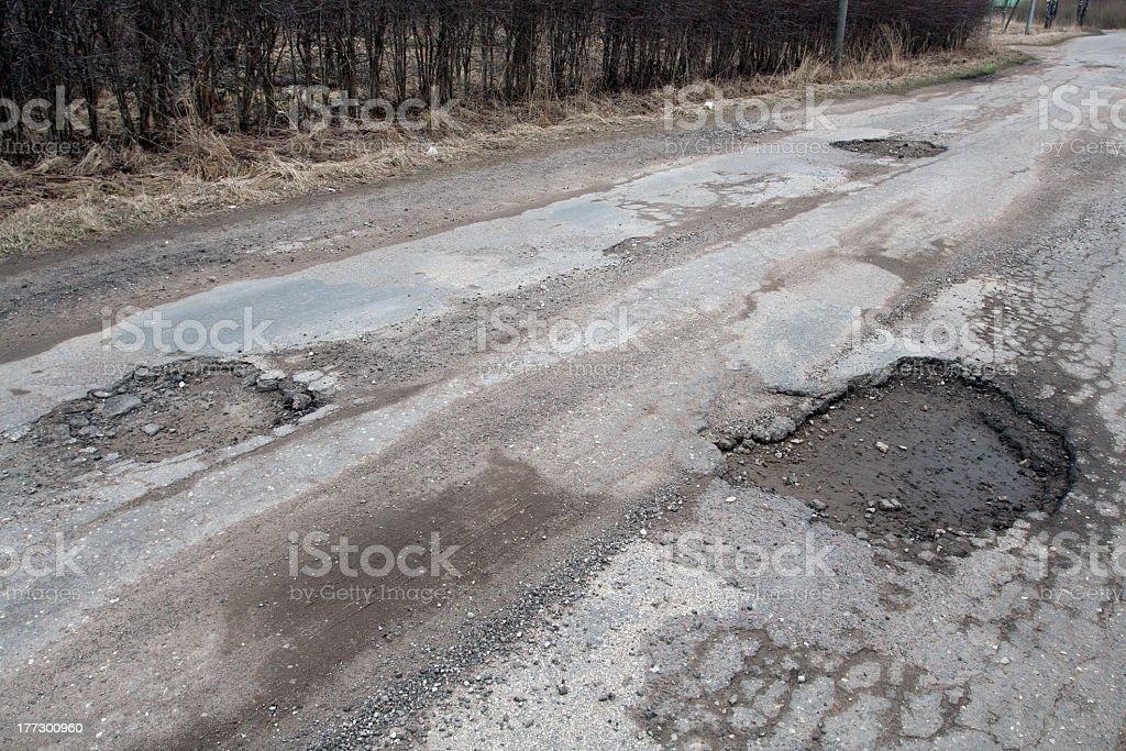 Damaged asphalt road after winter. stock photo
