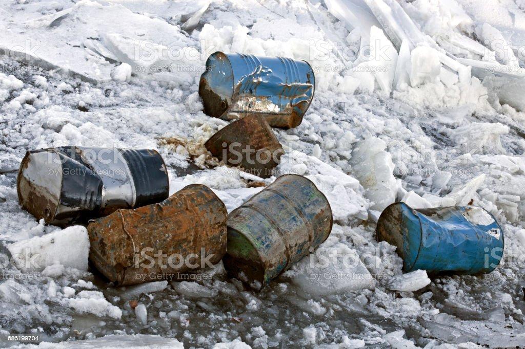 Damaged barrels in ice. stock photo