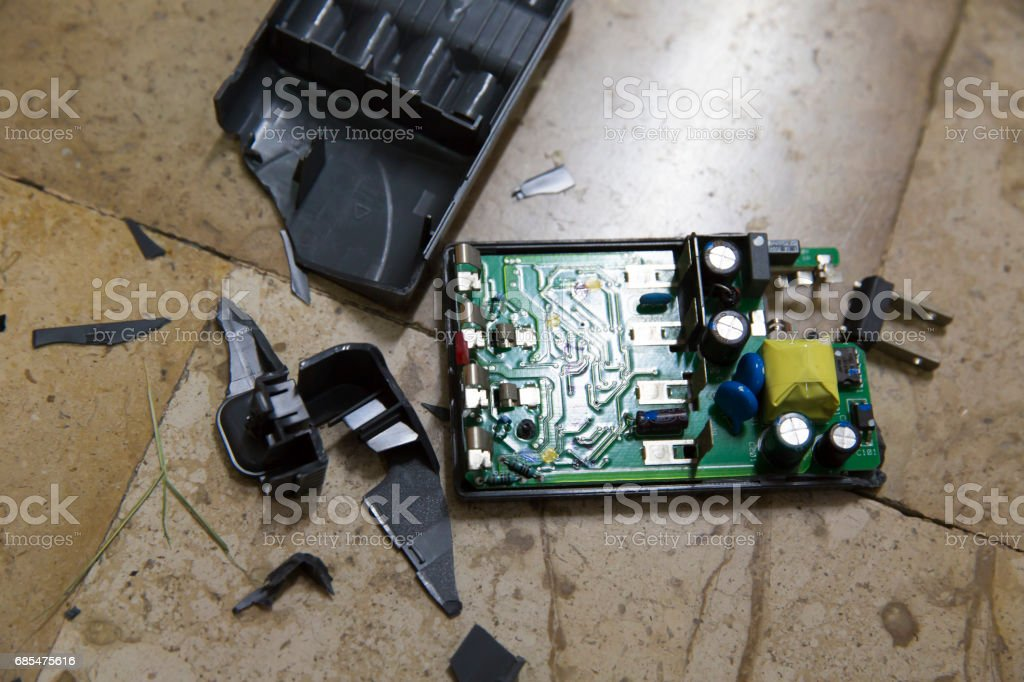 Damaged battery charger, due to fall down from the desk stock photo