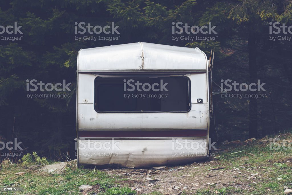 damaged car trailer in the woods stock photo