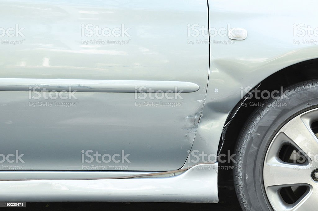 Damaged car with a dent near the wheel stock photo