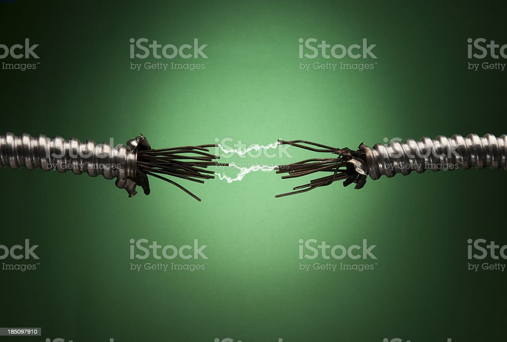 Damaged Conduit with Exposed Wires and Sparks stock photo