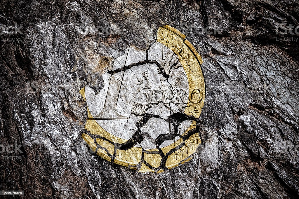 damaged euro coin on in a rock stock photo