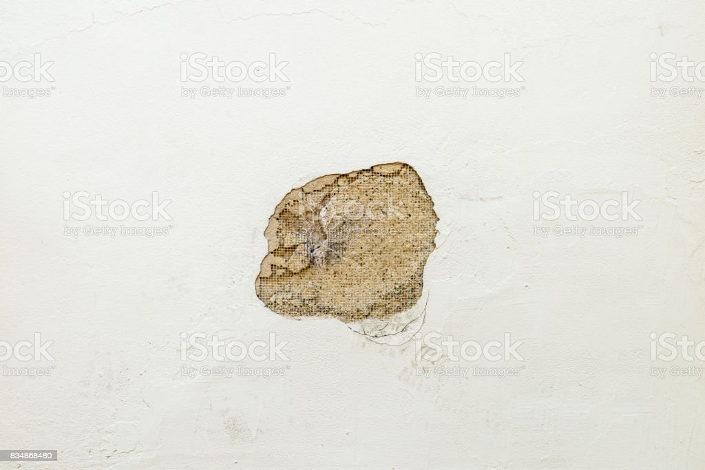 Damaged house wall with a hole in the plaster stock photo