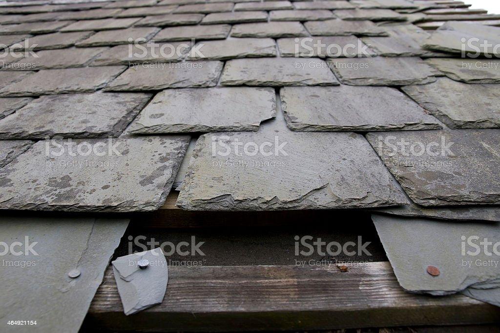 damaged roof with missing slates stock photo