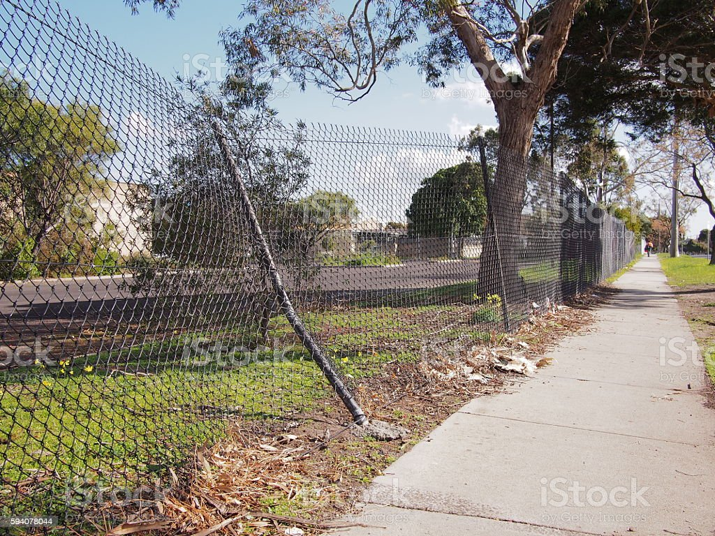 Damaged wire security fence after a car impact stock photo