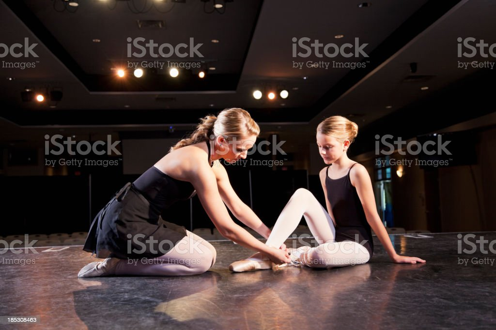 Dance instructor helping ballet dancer on stage royalty-free stock photo