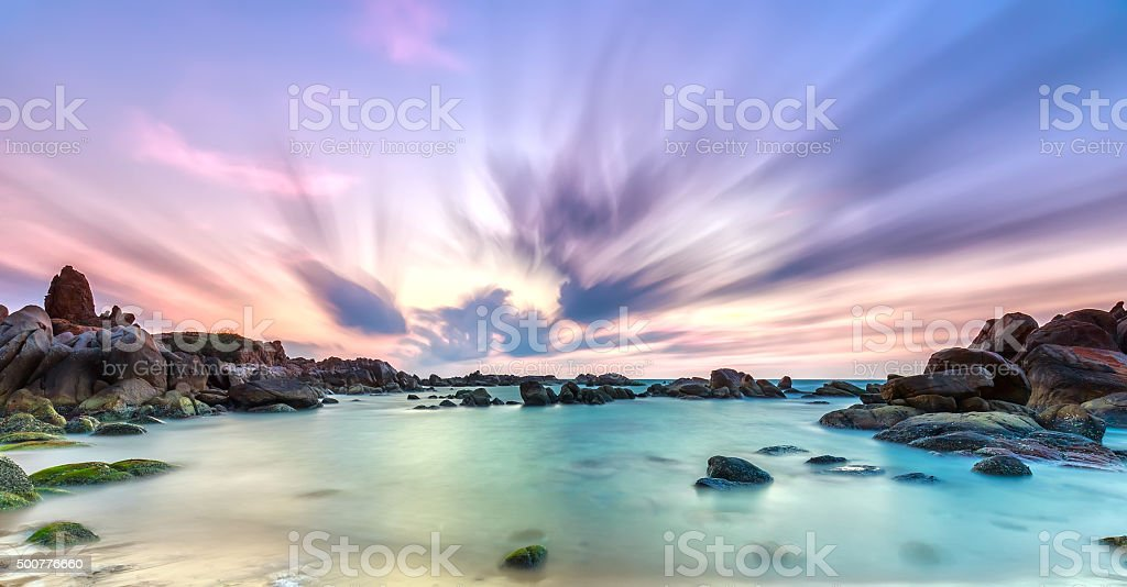 Dance of cloudy dawn on coastal reefs stock photo
