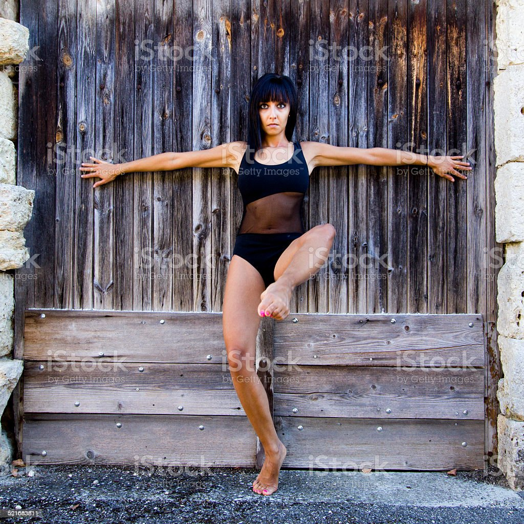 Dancer, arms outstretched, against a wooden door. stock photo