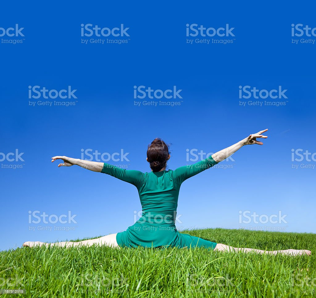 dancer doing splits on green grass with arms extended royalty-free stock photo