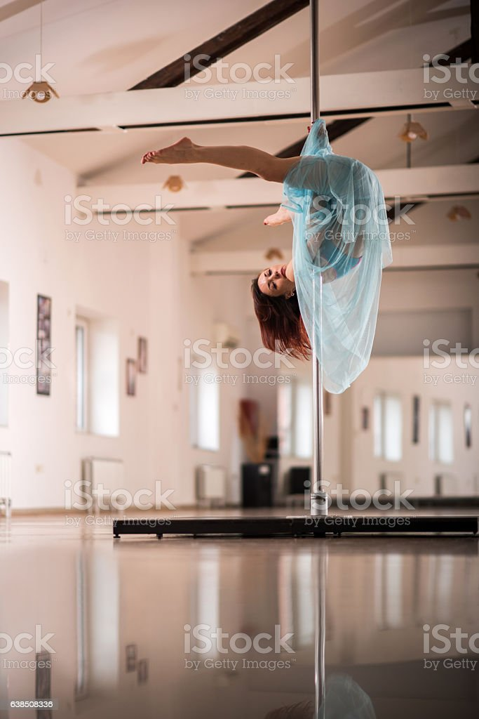 Dancer exercising pole dancing in a studio. stock photo
