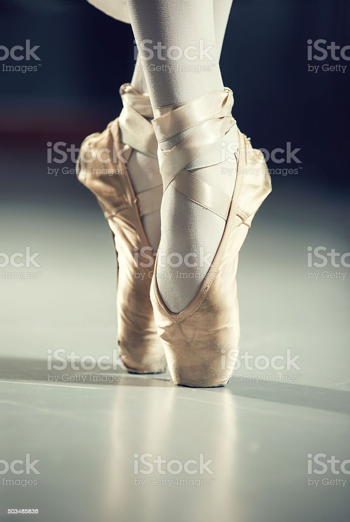 Dancer in ballet shoes, isolated on gray stock photo
