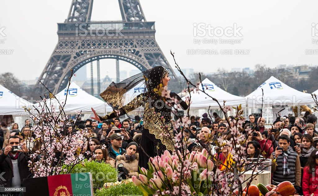 Dancer in traditional persian costume and Eiffel tower. Nowruz. stock photo
